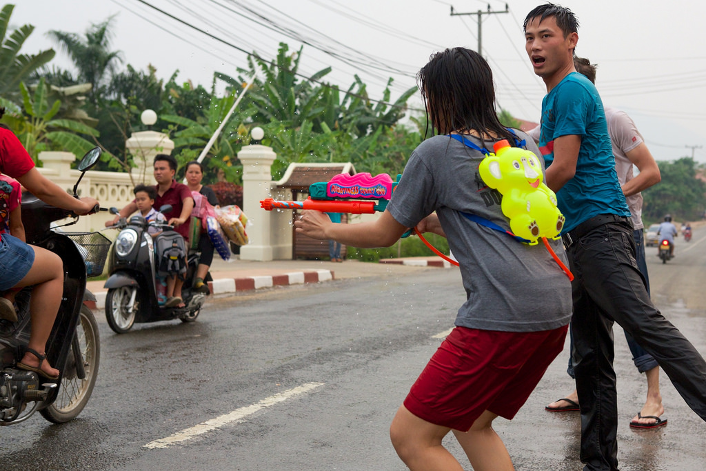 Girl shoots water at motorbike riders in Luang Prabang for Lao New Year