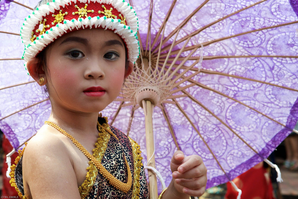 Little girl wearing traditional dress holding a purple umbrella at Lao New Year Parade