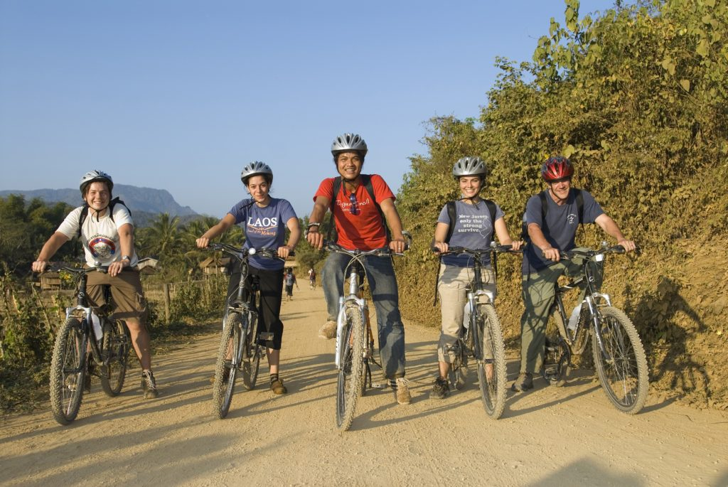Five cyclists on mountain bikes on tour with Tiger Trail Travel in Luang Prabang
