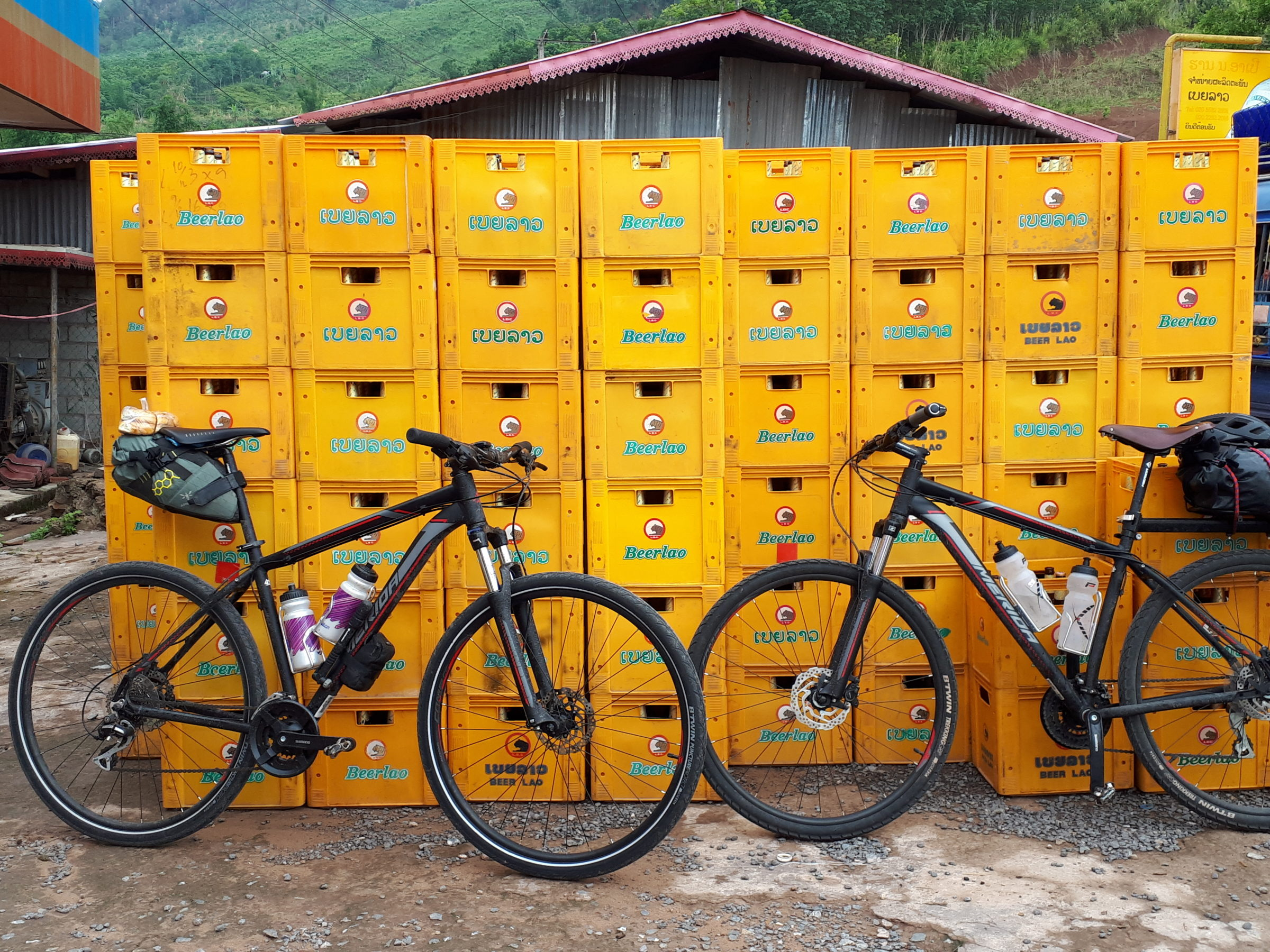 New mountain bikes Biking Laos in front of Beerlao crates